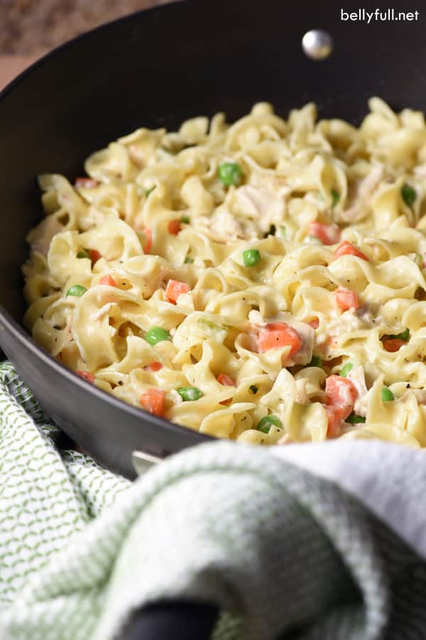cooked egg noodles, peas, carrots, and chicken in skillet