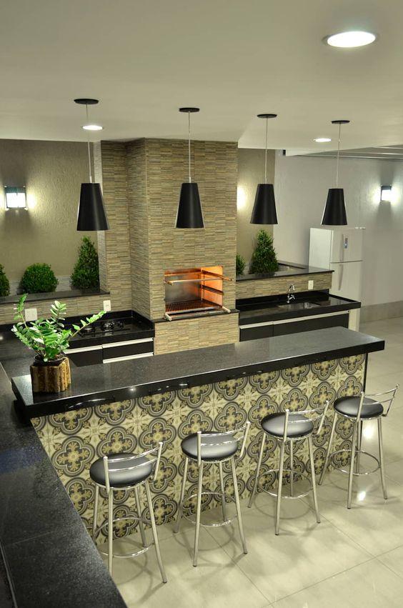 área externa de casa, com estilo moderno com luminárias pendentes pretas, bancada de granito e churrasqueira de pedras naturais.