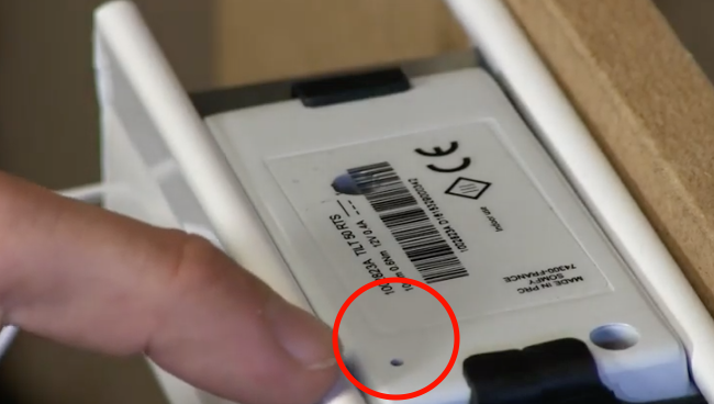 Reset button circled in red on the top of white Somfy tilt-only motor