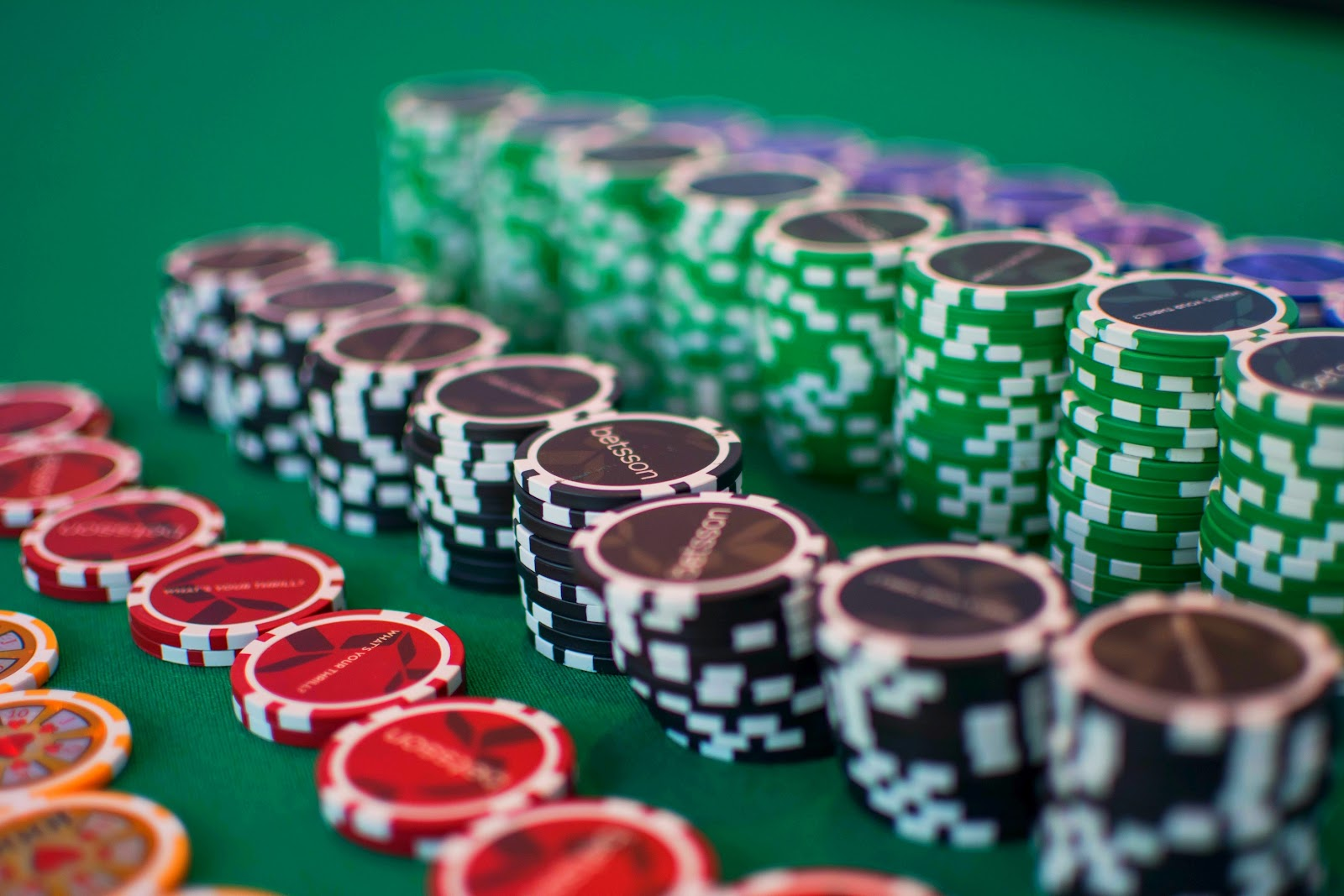 Rows of orange, red, black, green, and blue gambling chips sit on a green betting table