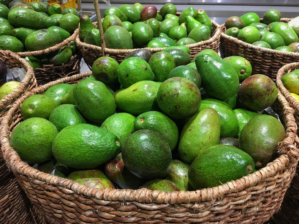 green fruits on brown woven basket