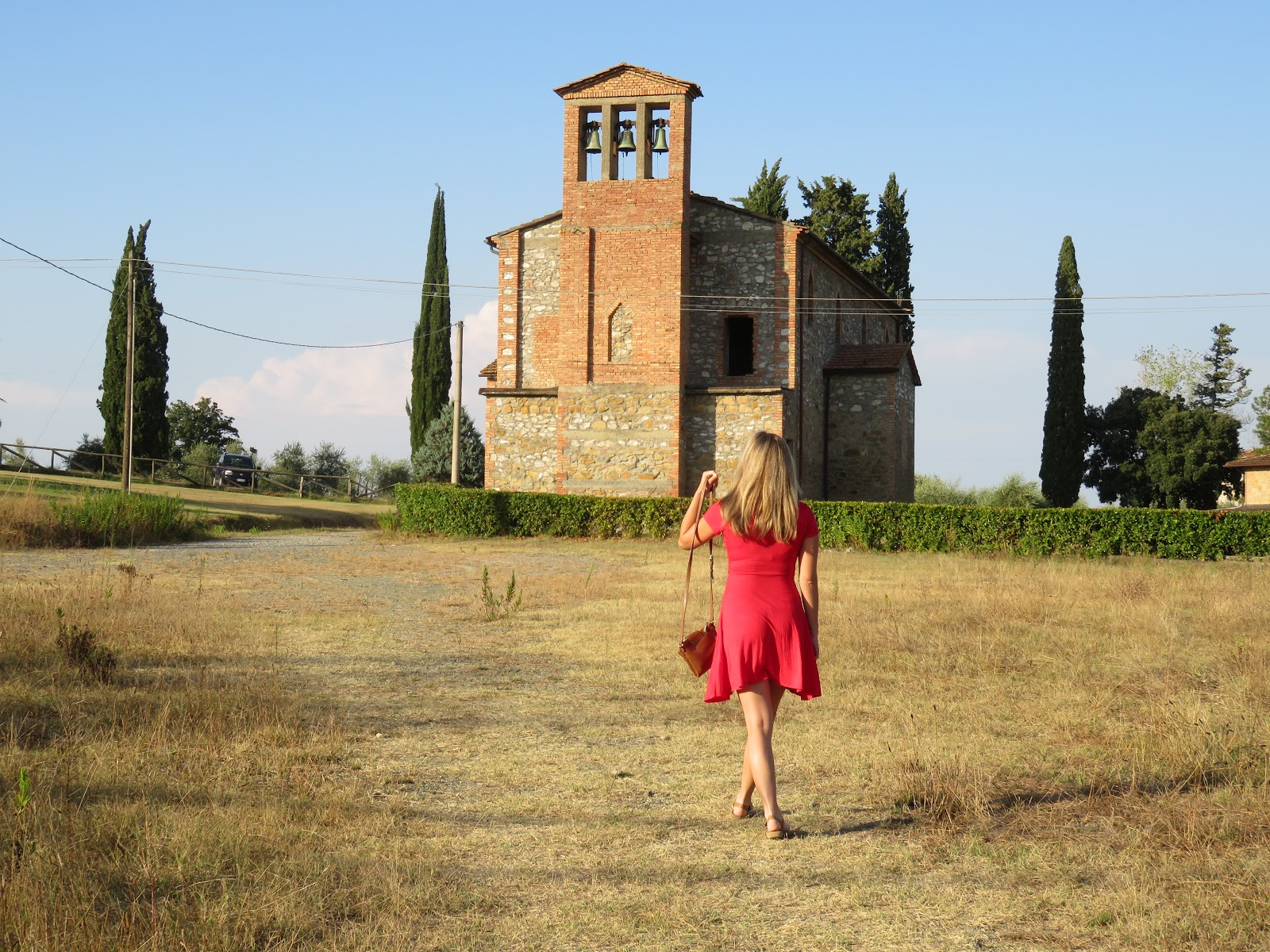 Young woman walking away across a field towards historic site