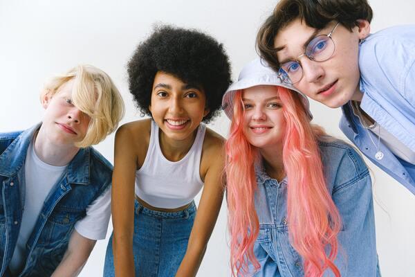Quatro amigos olhando para a camera, posando e sorrindo