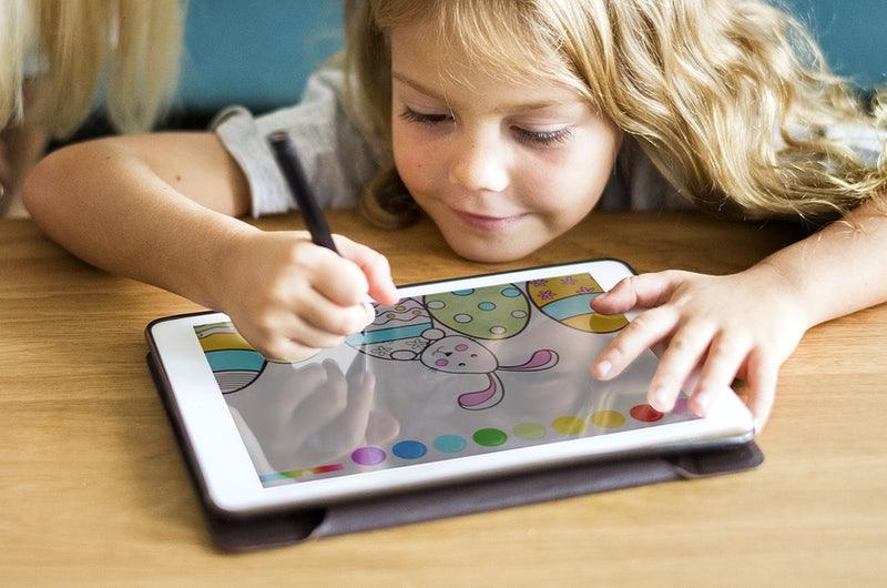 Uma menina  de cerca de 5 anos realizando uma atividade de pintura digital em um tablet, por meio de uma caneta digital. A imagem tem como objetivo ilustrar uma das possibilidades da gamificação na educação.