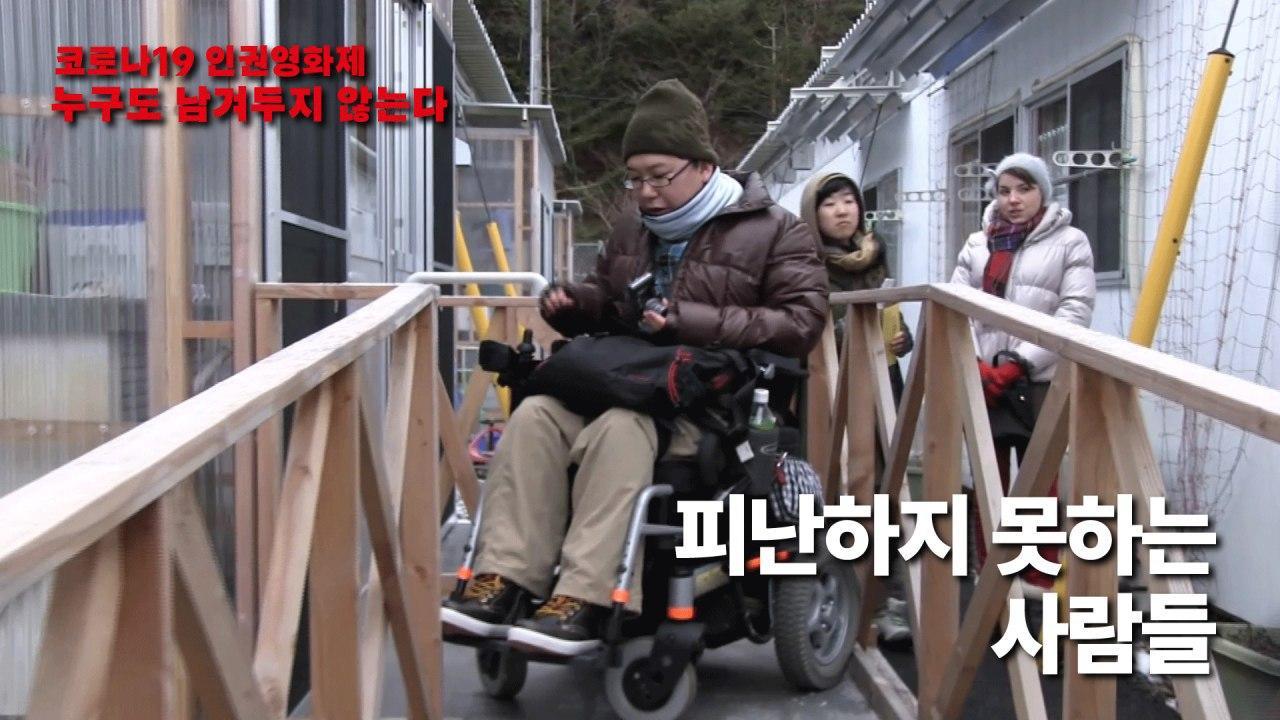 사진6. 영화 피난하지 못하는 사람들의 스틸컷. 좁은 통로 사이에 휠체어를 탄 사람이 있고 그 뒤로 두 명의 사람이 어딘가를 쳐다보고 있다.