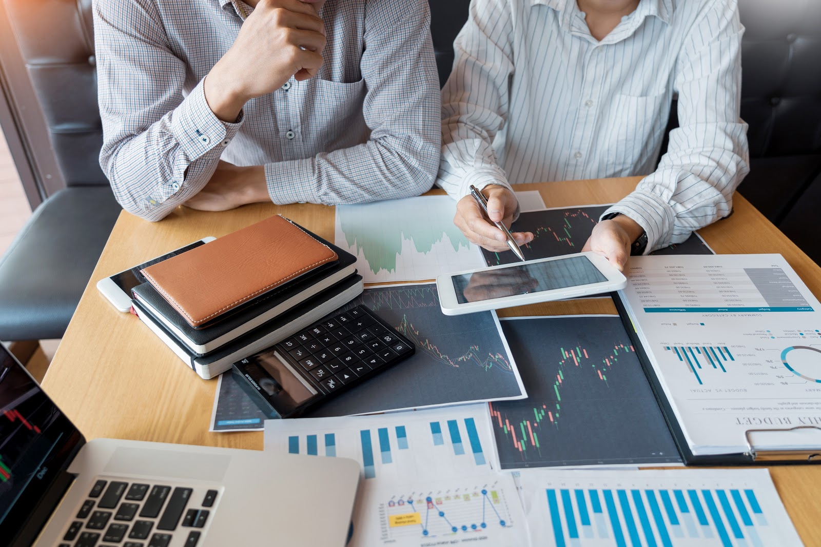 how to invest in dividend stocks: men talking with graphs and notebooks on the table