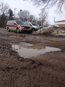 A large number of big potholes in the Quality Dairy parking lot are dangerous obstacles to drivers. Photo by Ariel Rogers.
