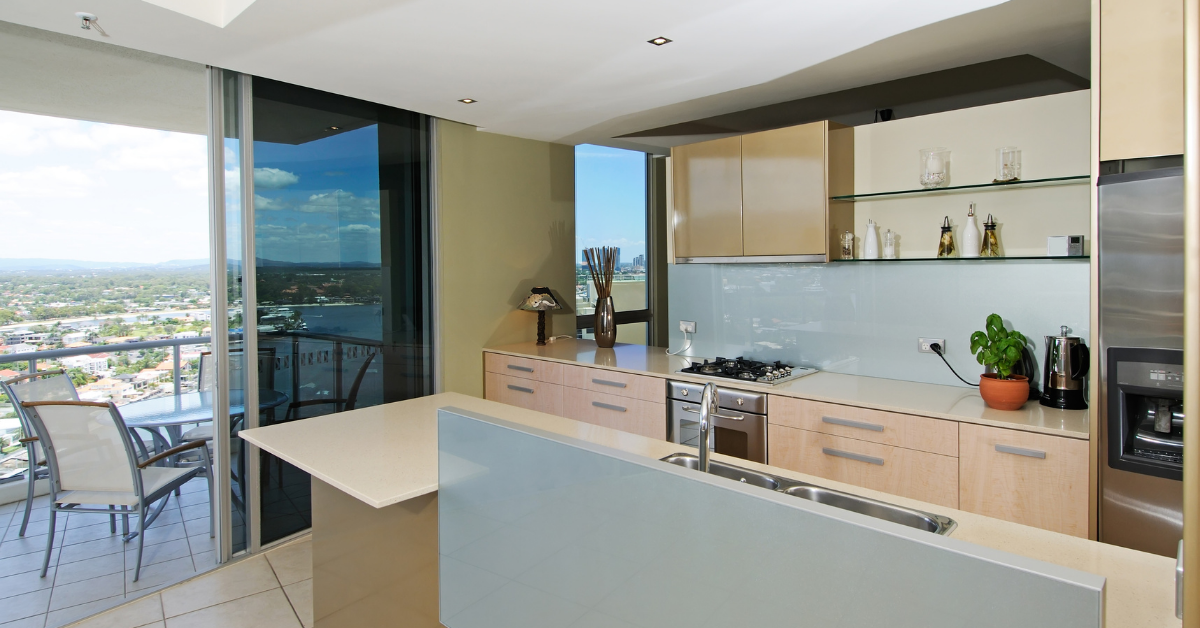 The kitchen of an apartment next to a balcony