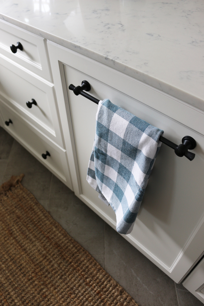 white shaker cabinets with matte black bar pulls, matte black knobs and a kitchen towel