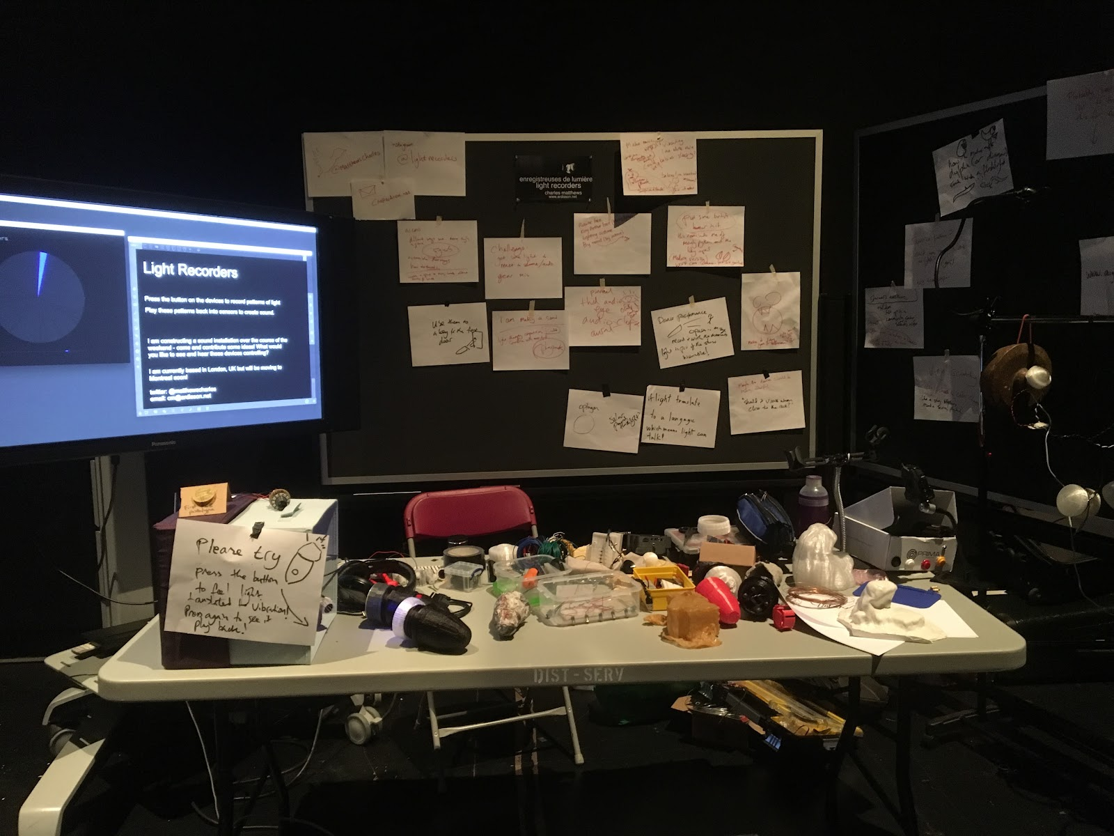 A table covered with 3D printed flashlights and hand-written instructions sits next to a screen showing a wheel to represent intensity of light, with visitor feedback and ideas pinned to a board behind.