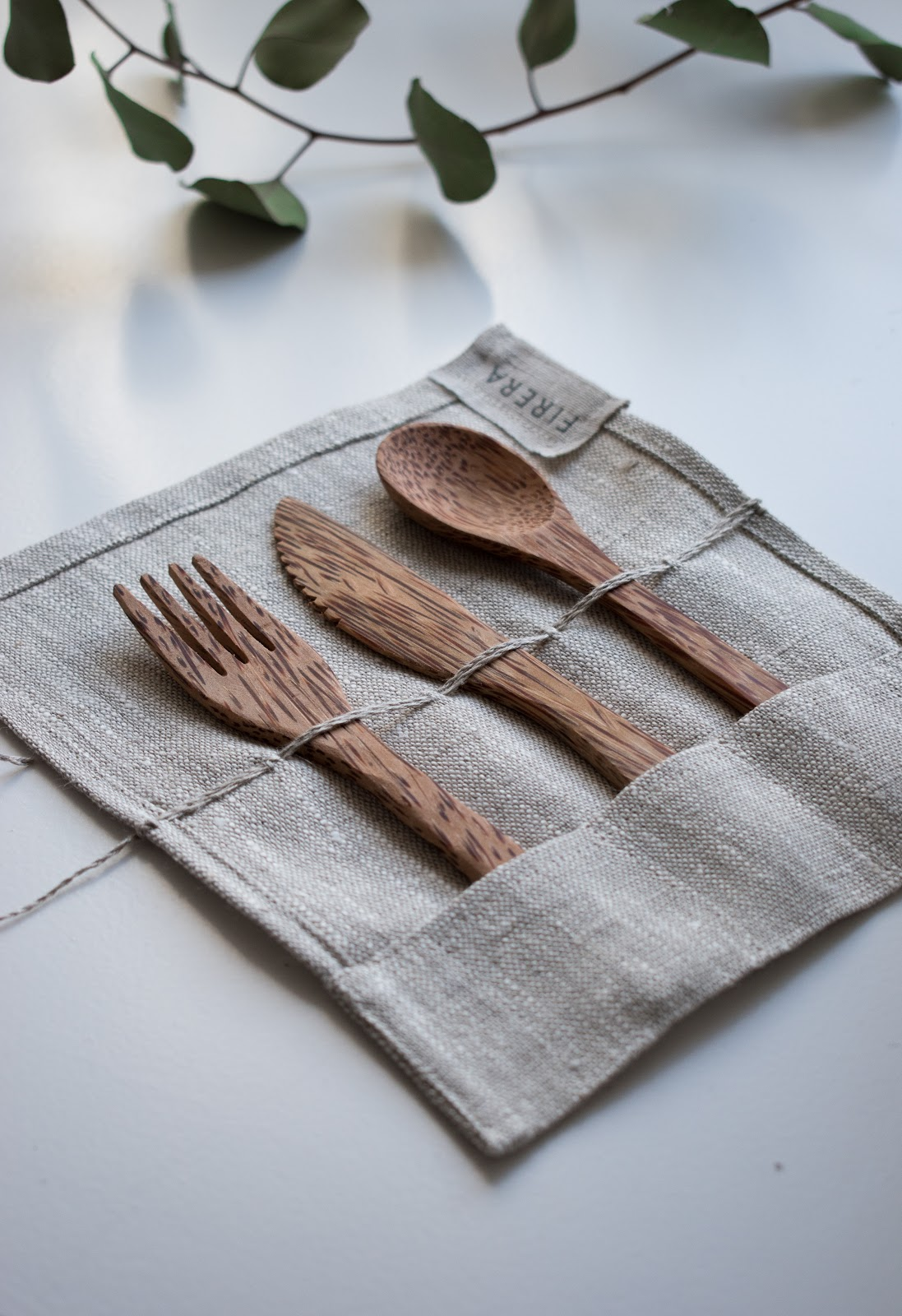 Wooden reusable utensils, fork, knife, and spoon, placed on a table. Reduce waste by bringing your own cutlery