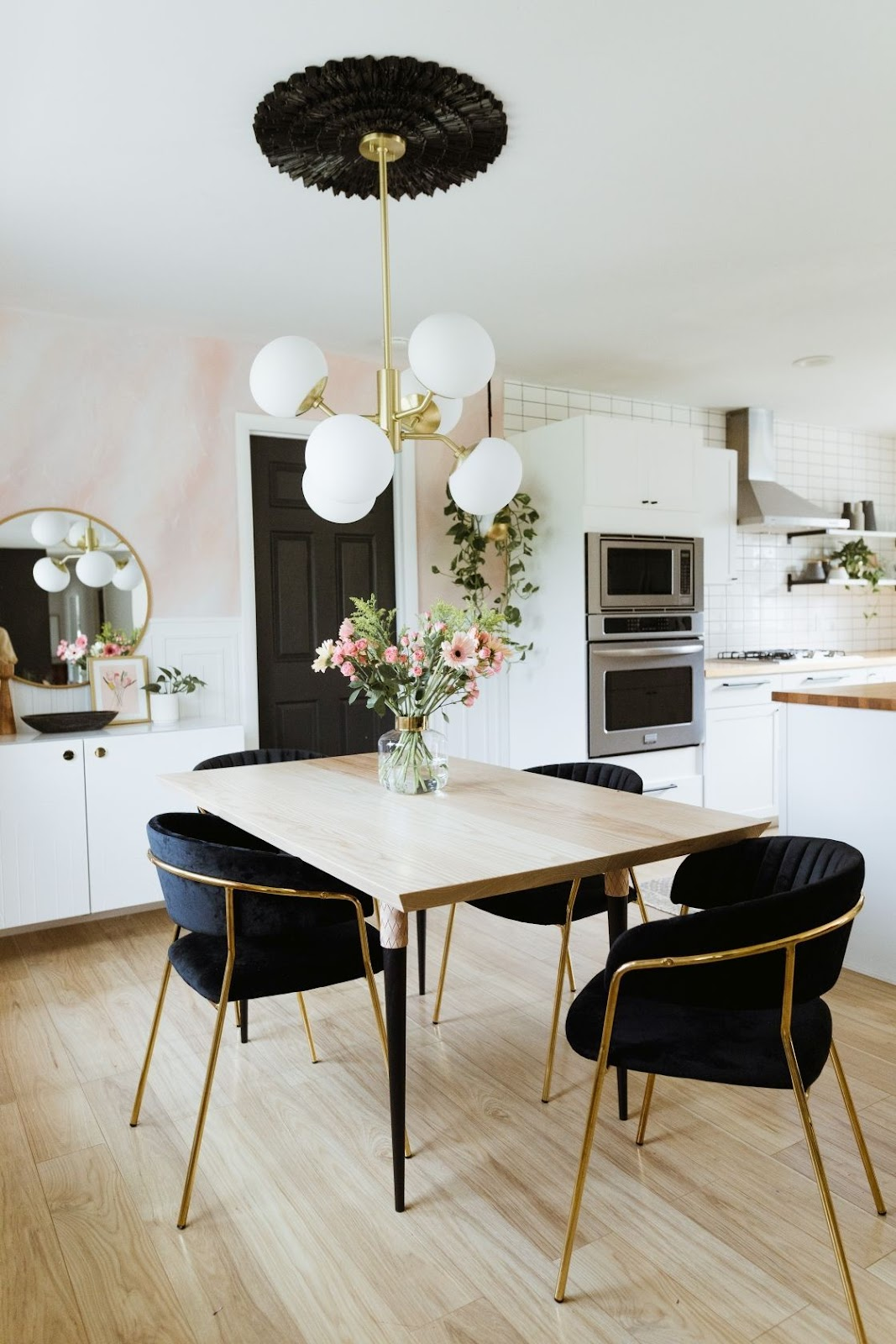 dining area next to a white kitchen with wood table, black chairs with gold accents, wood floors and a unique gold and white pendant light