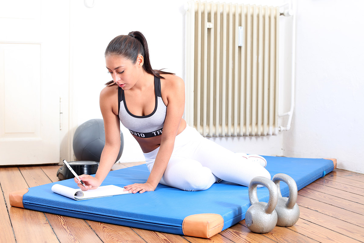 Best pea protein powder: Athletic woman writing in a protein intake journal