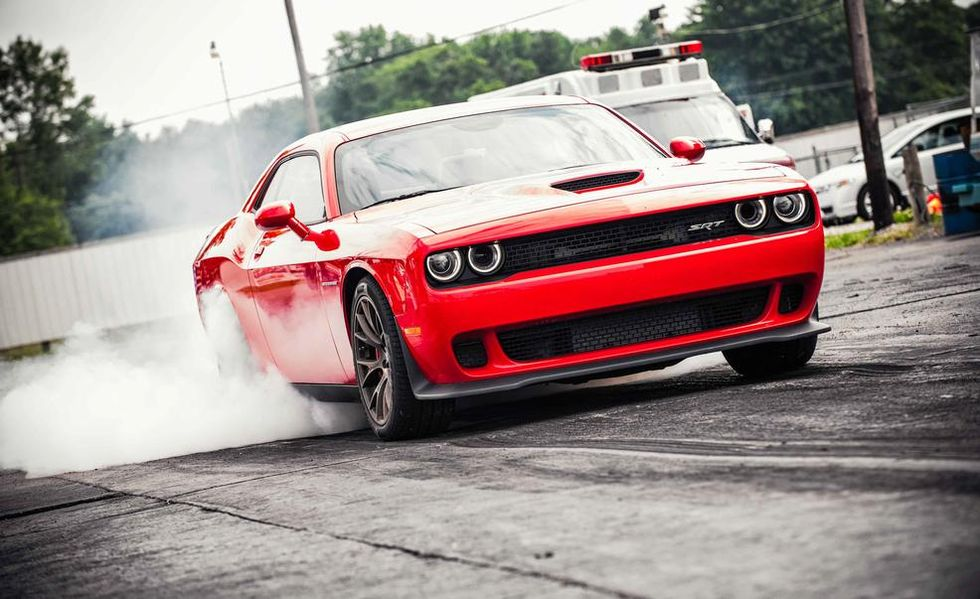 A 3rd Generation Dodge Challenger with additional aggressive styling doing a burnout with smoke pouring from the rear wheels.