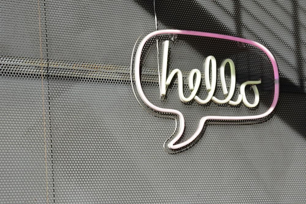neon sign in speech bubble shape saying hello