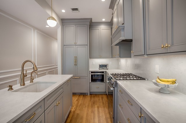 grey galley kitchen with grey shaker cabinets, brass hardware, wood floors and grey paneled appliances