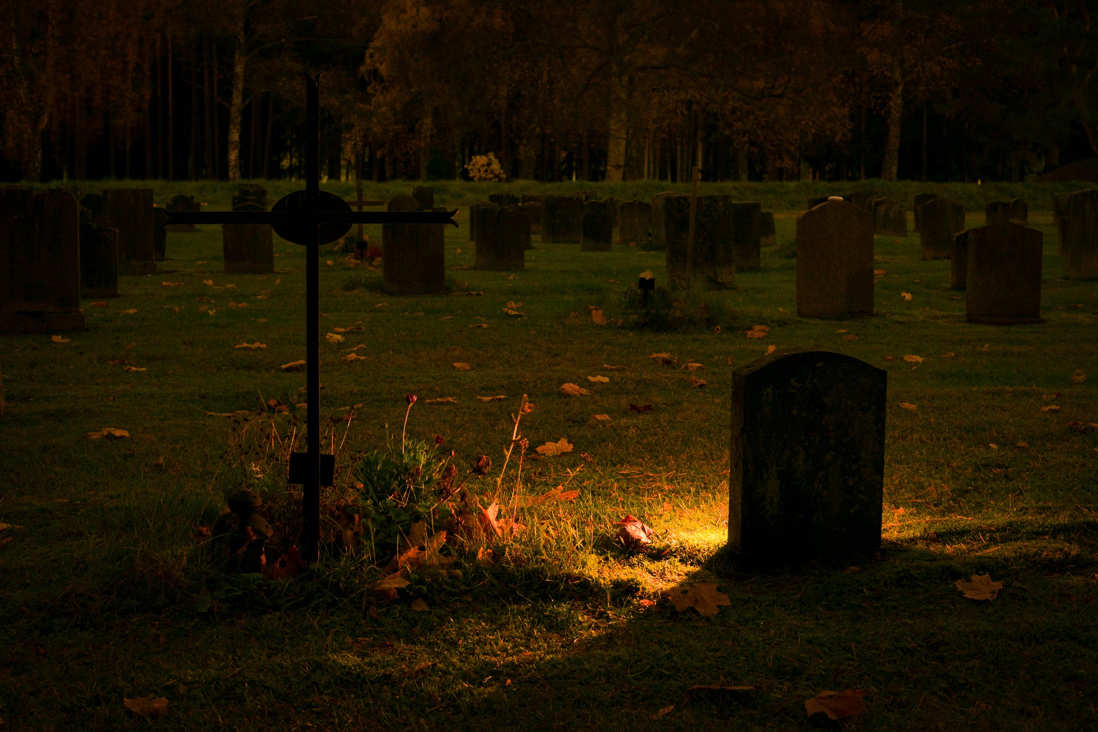 A silhouette of a gravestone in a graveyard. Stock image