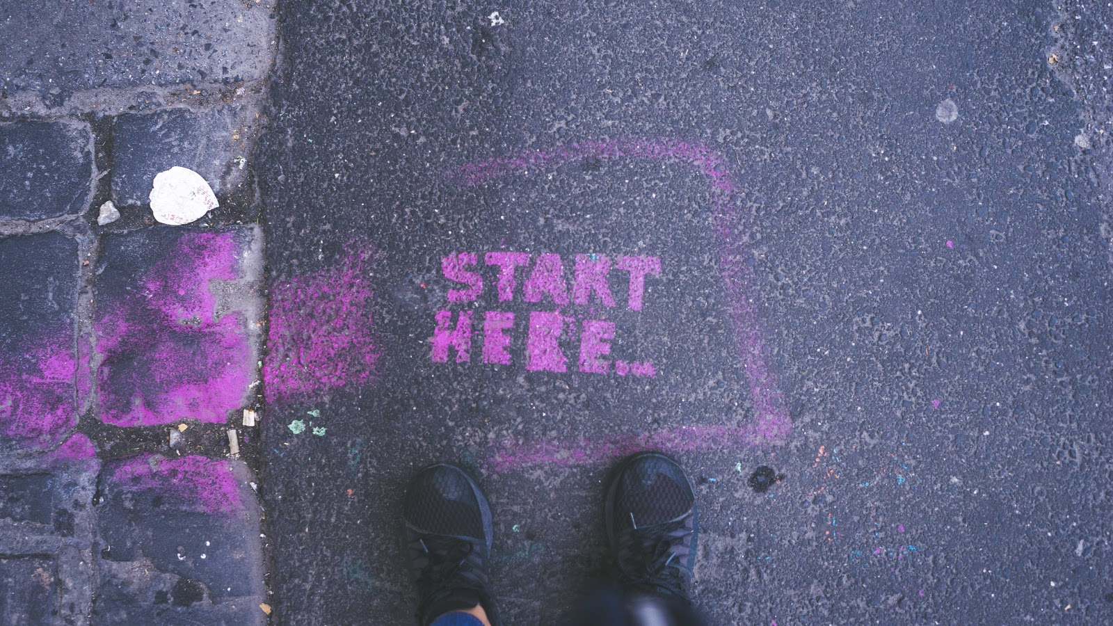 Two feet on a road with text saying start here