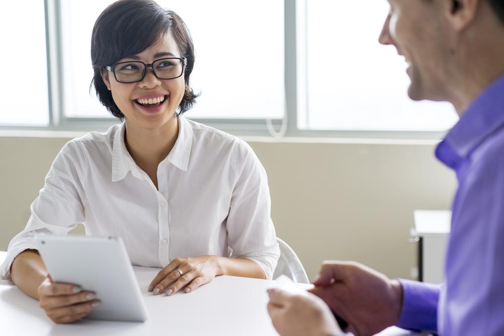 Uma mulher conversando com um homem em uma mesa de escritório.
