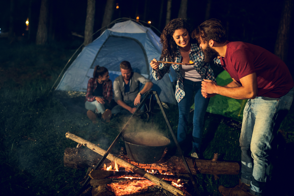 Group of people camping and cooking food over a campfire.