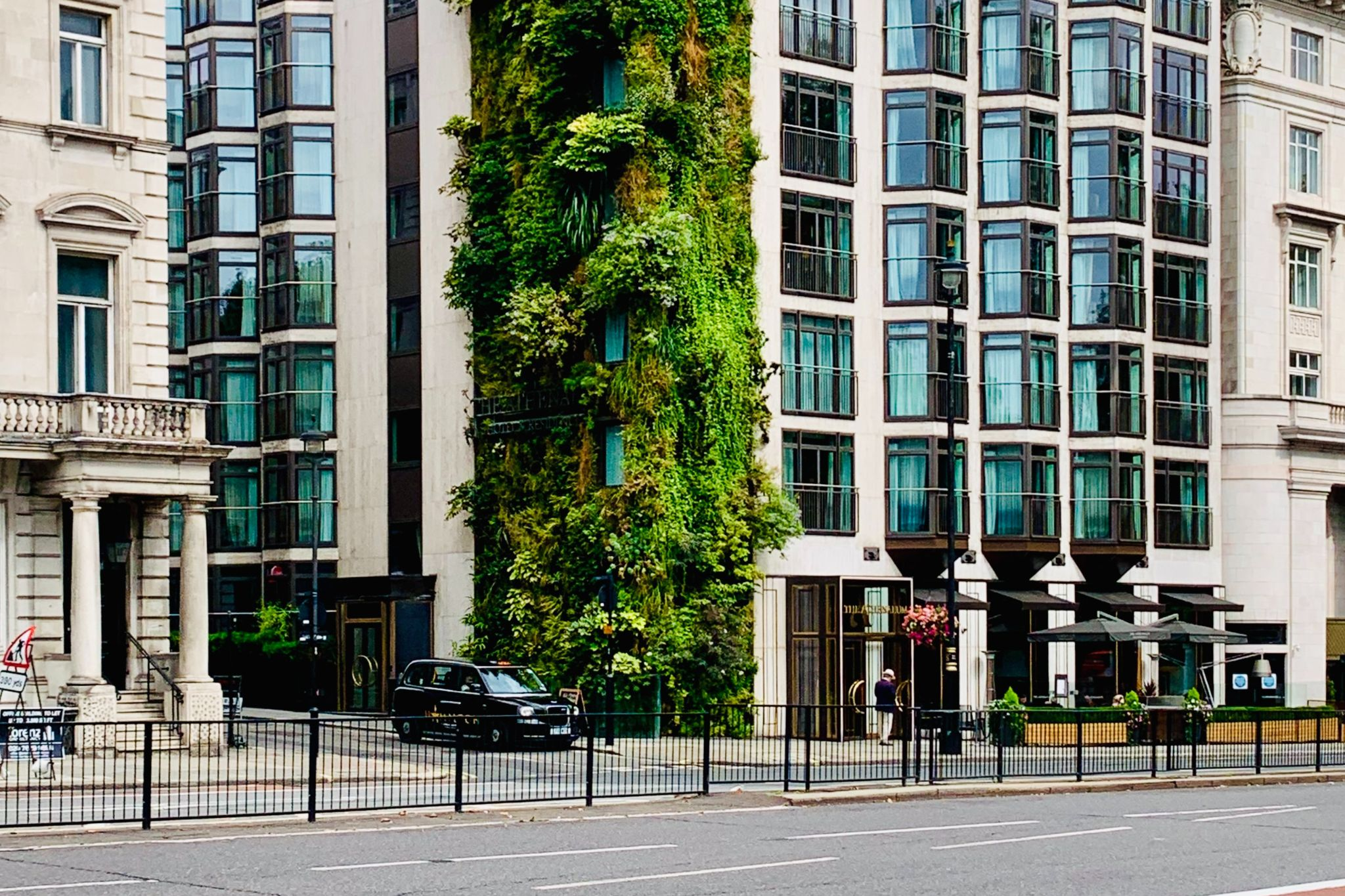 A green building in the middle of a city with a plant-filled exterior wall.