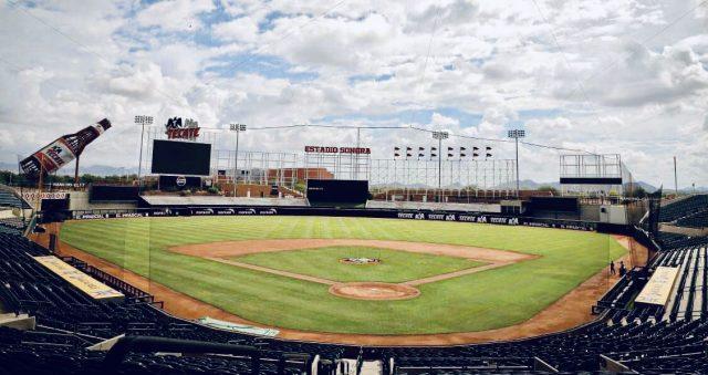 Un jugador de béisbol con espectadores en las gradas de un estadio  Descripción generada automáticamente con confianza media