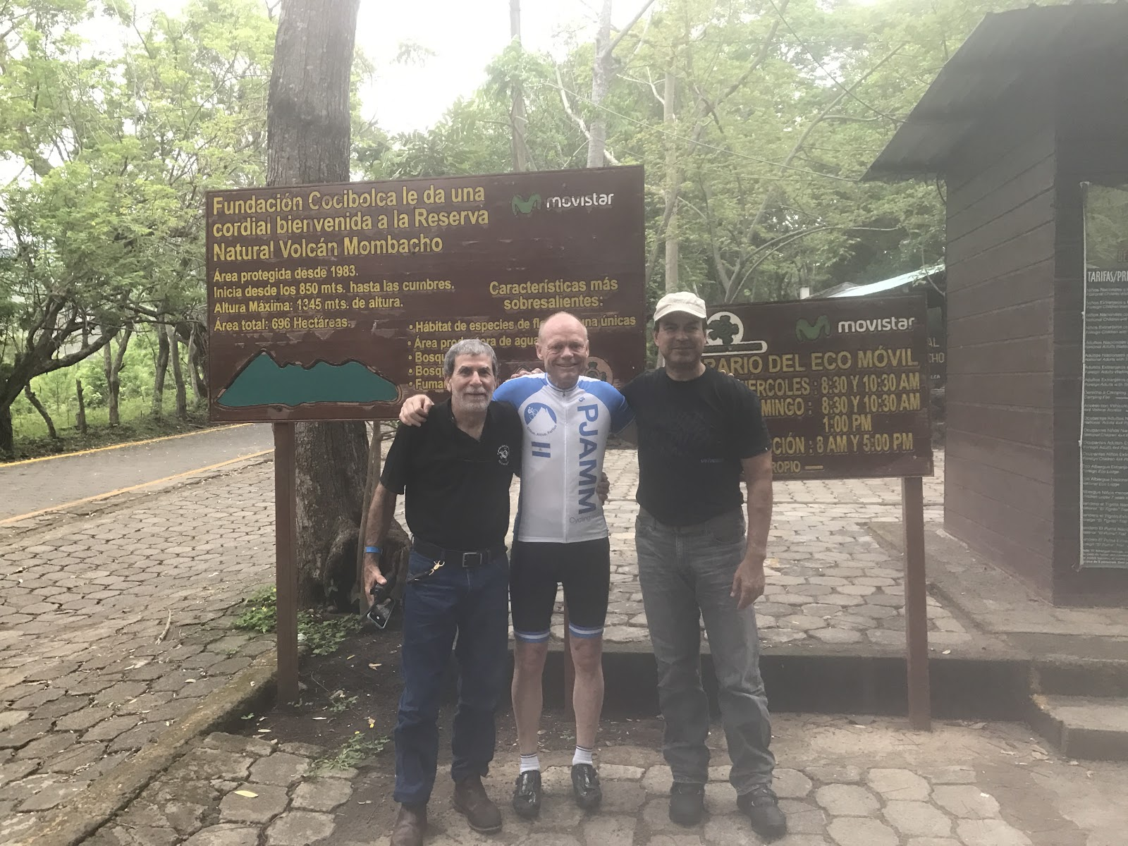 Biking up Mombacho Volcano - with the director of the preserve at bus stop, park sign