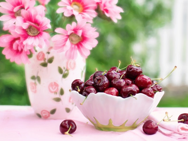 fancy bowl filled with cherries next to vase with pink flowers