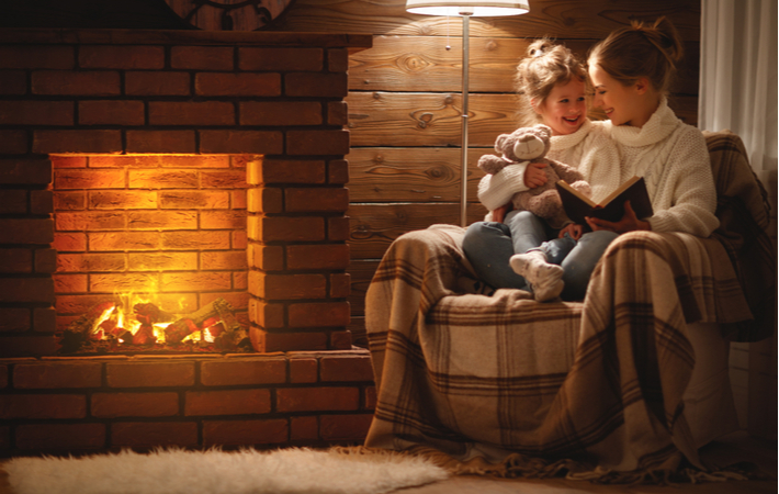 mother and daughter reading a book in front of a fireplace