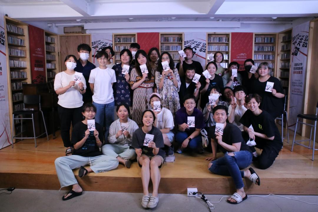 """사진4. 라이브토크 1부를 마치고 찍은 단체 사진. 출연진과 연분홍TV 팀, 서울인권영화제 활동가들이 """"코로나19 인권영화제: 누구도 남겨두지 않는다"""" 엽서를 손에 들고 무대 위에서 환하게 웃고 있다."""