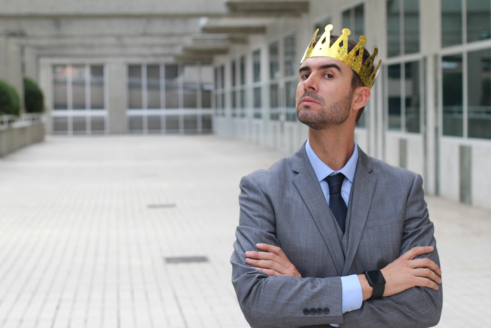 A man looking staring at the camera overly confident wearing a crown