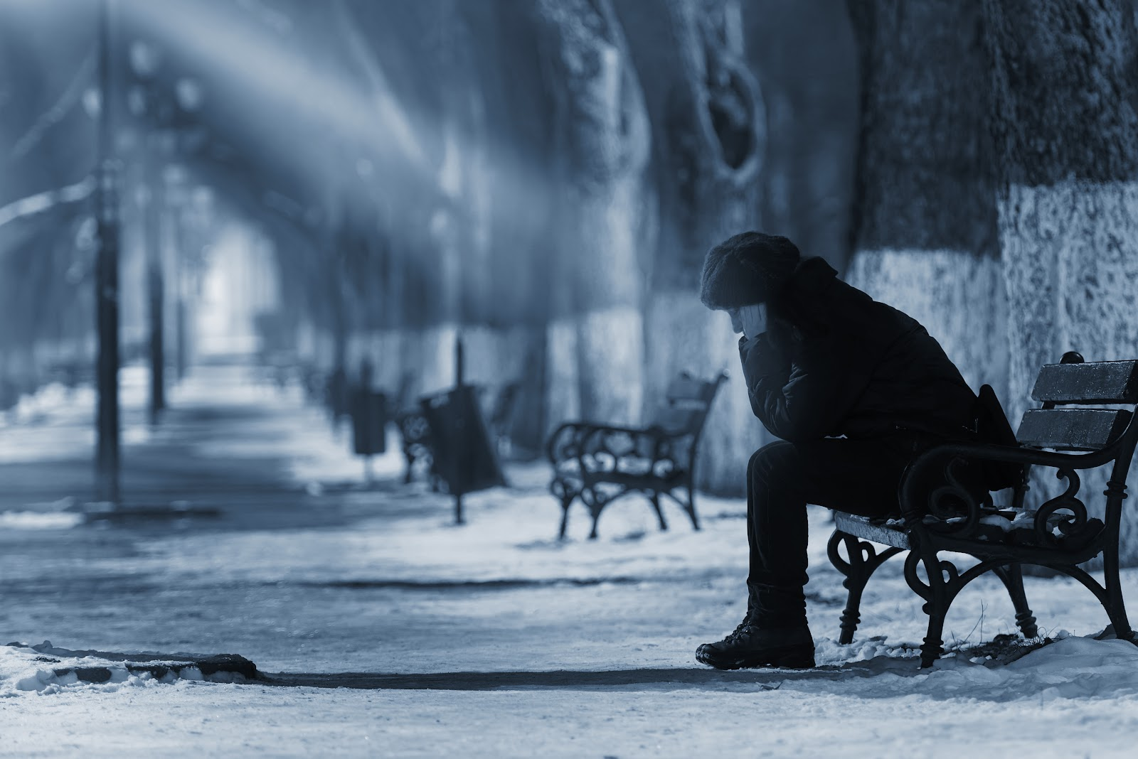 Woman with winter blues sitting on a snowy bench