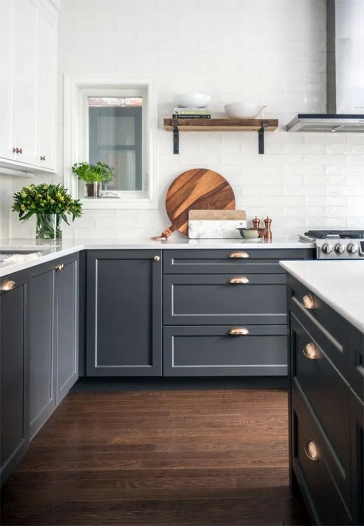 dark base shaker cabinets and white upper shaker cabinets create a beautiful contrast in this contemporary kitchen. this space also features dark wood floors and a white tile backsplash