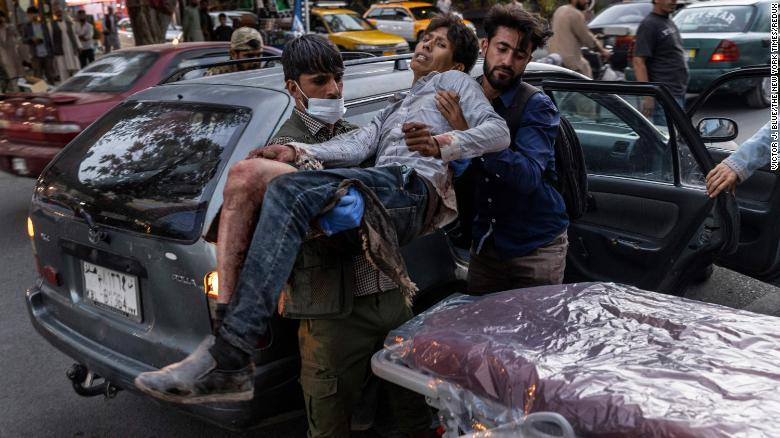 A person wounded in the explosion outside the airport arrives at a hospital in Kabul.
