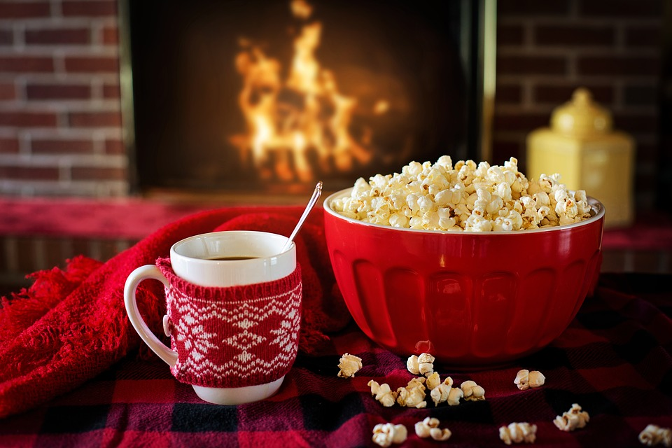 A coffee cup with a red blanket around it and a red bowl filled with popcorn sits in the foreground closest to the camera.  Another red blanket is behind them. A roaring fire is blurred in the background.