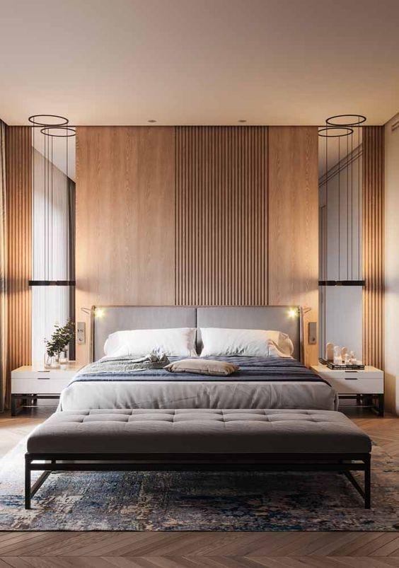 Quarto de casal com cabeceira estofada cinza, na parede de fundo um painel de madeira, piso de madeira e criados mudo brancos.