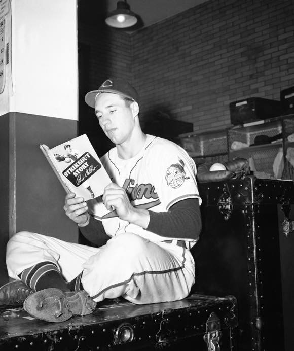 "Cleveland Indian pitcher Bob Feller reads a copy of his book, ""Strikeout Story,"" as he sits in the Cleveland dressing room, May 5, 1947 photo credit: AP Images"