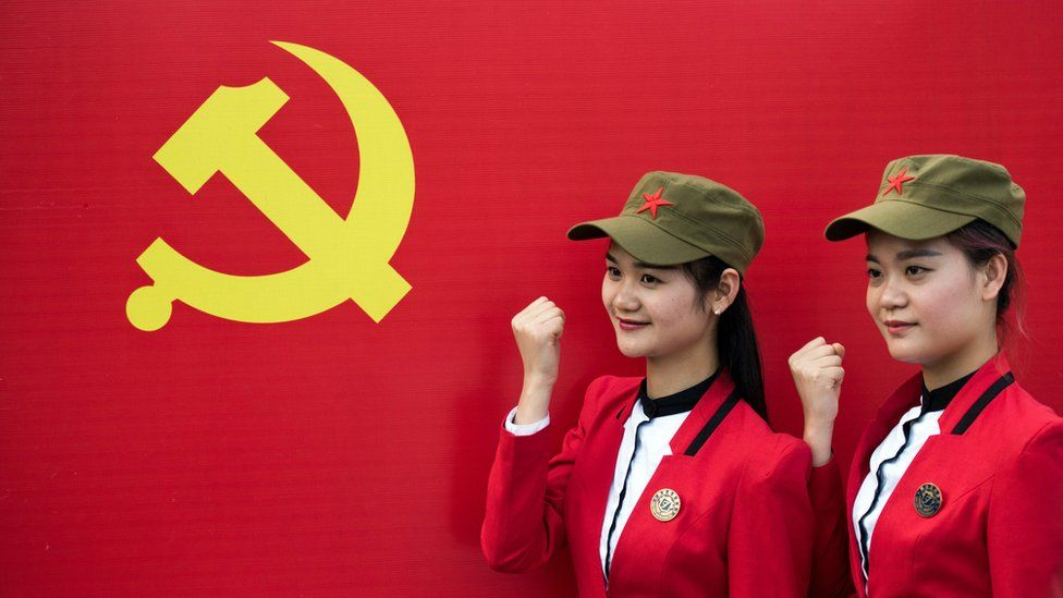 Members of the Communist Party of China in front of the hammer and sickle.