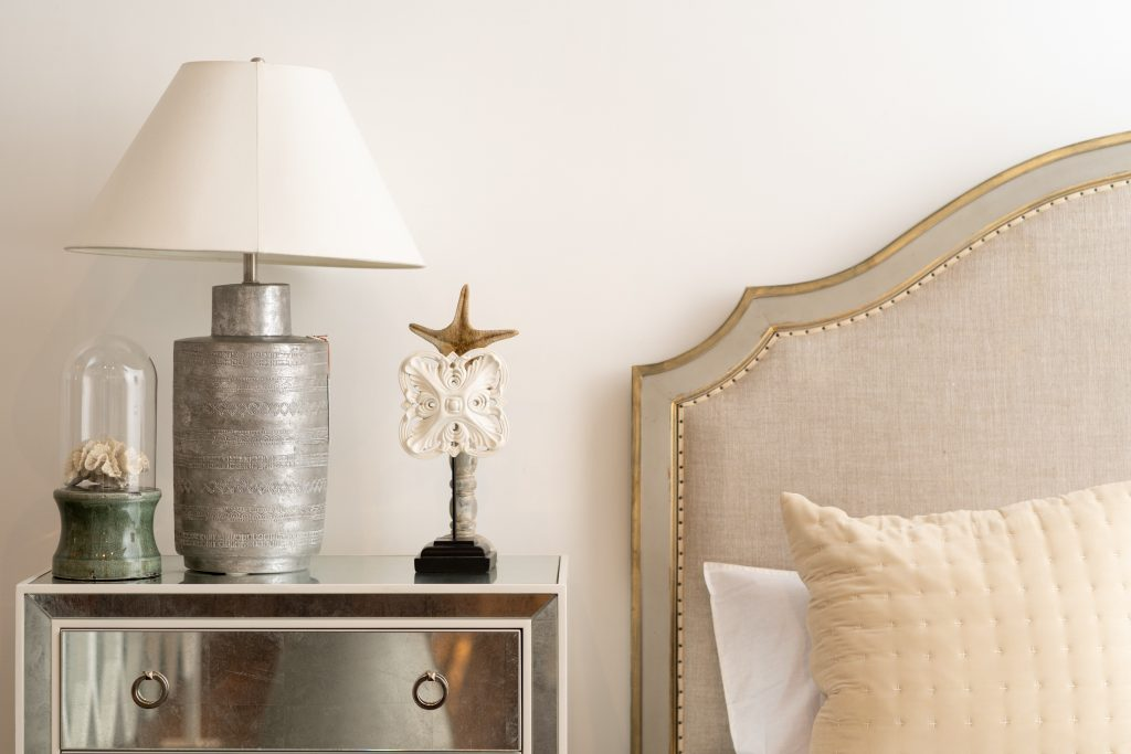 bedframe with pillow beside lamp on table and ornaments