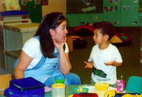 An instructor listening to a child explain something
