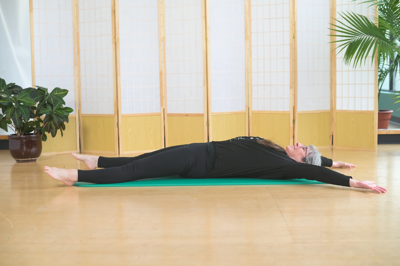 A MOVE trainer doing a full body stretch on the floor.