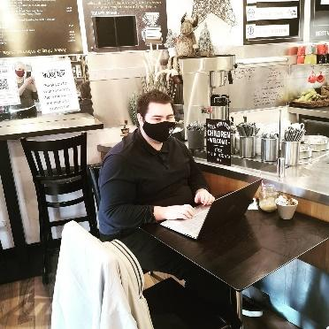 A person sitting at a table  Description automatically generated with low confidence