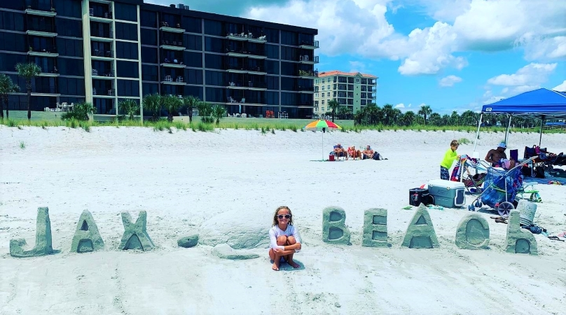a kid sits on Jacksonville Beach in front of a sand sculpture