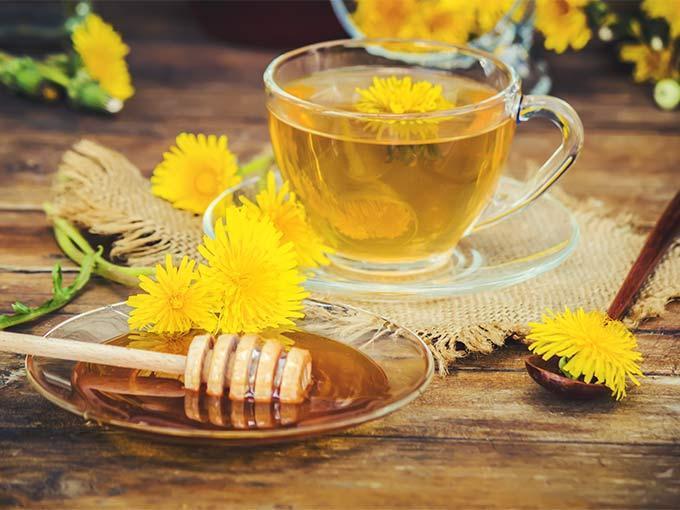 Löwenzahntee in einer gläsernen Tasse und neben einer Schale Honig steht auf eiem Tisch - Diabetiker können auch mithilfe von Tee ihren Blutdruck senken.
