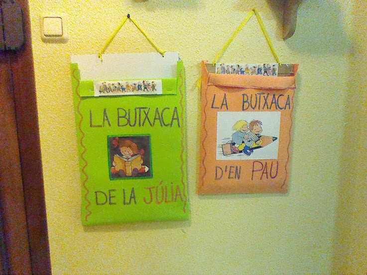 Bolsillos o portafolios infantiles acabados y colgados en la pared.