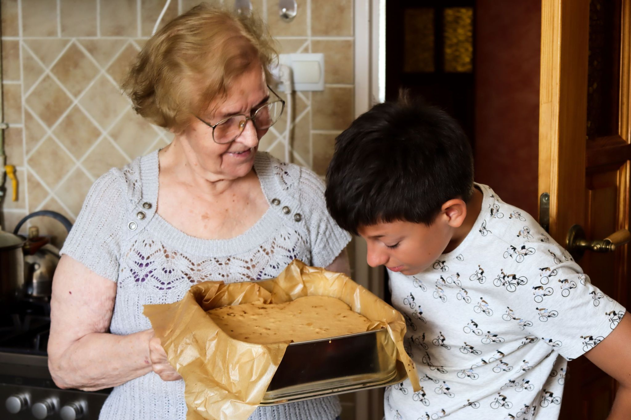 older-woman-bakes-cake-for-young-boy