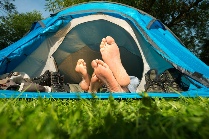 People sleeping in tent with their feet hanging out