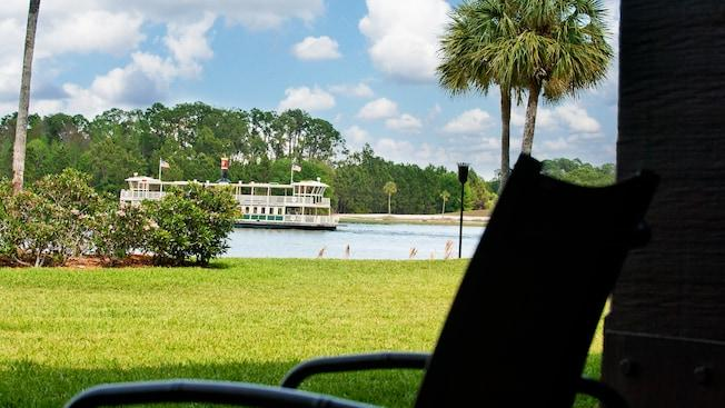 A patio with a chair and, beyond, a garden and a boat on Seven Seas Lagoon