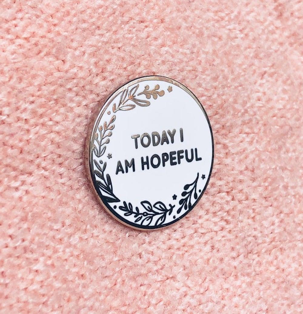 """An enamel pin from Clara and Macy that reads """"Today I Am Hopeful."""""""