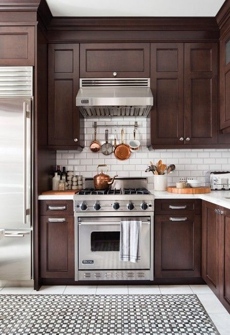 kitchen with brown shaker cabinets, white subway tile backsplash and stainless steel appliances